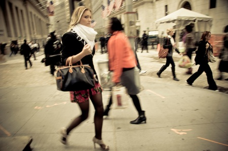 A trendy girl walks on Wall Street in front of the New York Stock Exchange, Manhattan, New York, 2009.